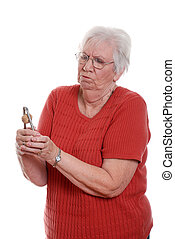 Senior struggling to open nut - isolated Senior woman...