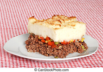 serving of shepards pie on red and white tablecloth