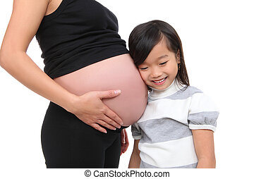 Girl Listening to Baby Pregnancy - A cute young asian girl...