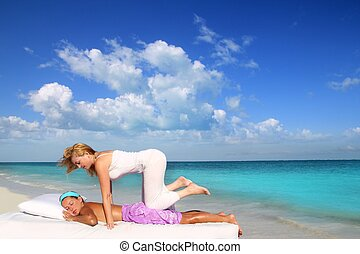 Caribbean beach therapy shiatsu massage on knees women in...