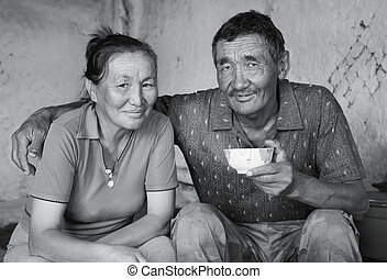 A man and a woman of Asian appearance have tea
