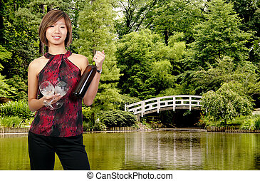 Woman with Wine - A beautiful Asian woman holding a wine...
