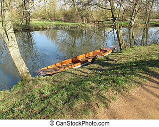 Empty punt moored on tranqil river - Empty punt moored on a...