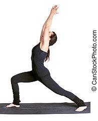 yoga excercising virabhadrasana - full-length portrait of...