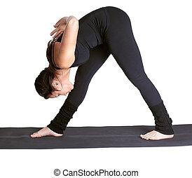 yoga excercising parshvottanasana - full-length portrait of...