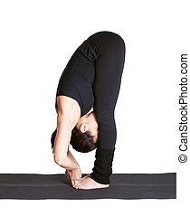 yoga excercising padangushthasana - full-length portrait of...