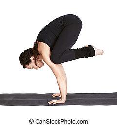 yoga excercising bakasana - full-length portrait of...