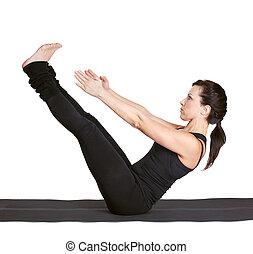 yoga excercising navasana - full-length portrait of...