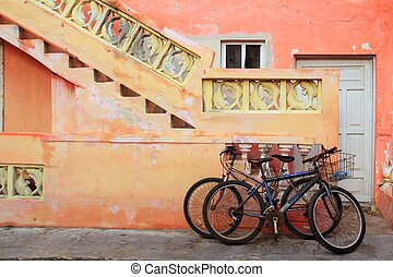 bicycles on grunge tropical Caribbean orange facade -...