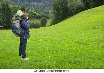 kid with backpack on a trip in a green field