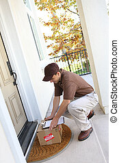 Delivery Man - A young delivery man delivering a package to...