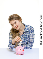 piggy bank - young woman safing her money in a piggy bank