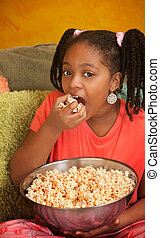 Little Girl Eats Popcorn - Little African American girl in...