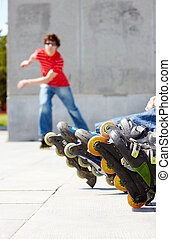 Roller skating - Young guy skateboarding outdoors