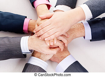Strength - Image of business people hands on top of each...
