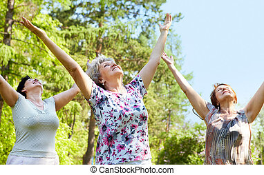 Praise - Portrait of three aged women with her arms raised...
