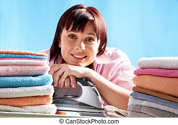Cheerful housewife - A smiling woman with an iron and heaps...