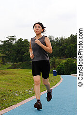 Woman jogging - A woman jogging at a park