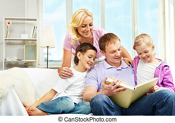 Family reading - A family of four sitting on sofa and...