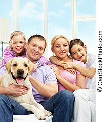 Family with dog - A young family of four with a dog sitting...