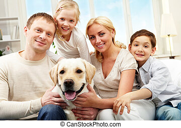 Average family - Portrait of a happy family sitting on sofa...