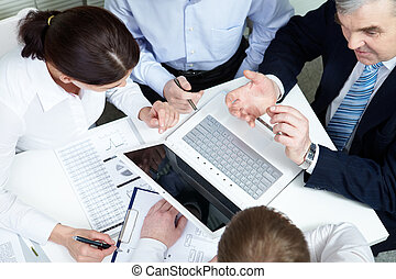 Planning team - A business team of four sitting at table and...