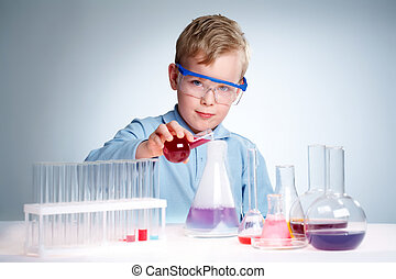 Young experimentalist - A little boy pouring liquid into a...