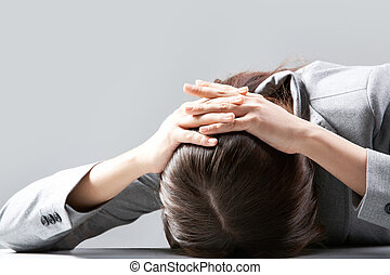 Banging against table - A young woman hiding her face on...