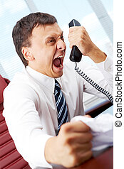 Angry man - An angry manager screaming in telephone receiver...