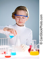 Little scientist - A little girl pouring liquid into a flask