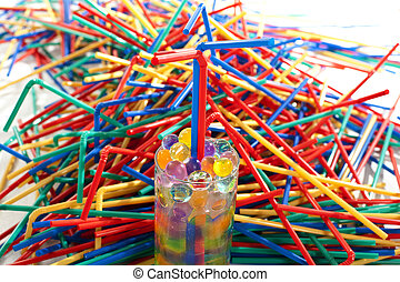 messy plastic bulk of straws surrounding a glass with...