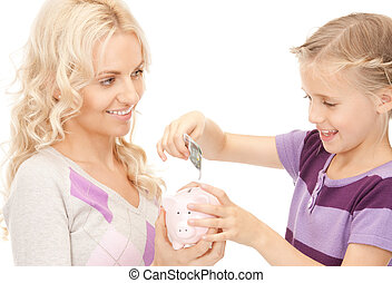mother and little girl with piggy bank - picture of mother...