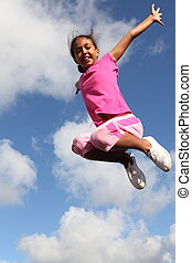 Excited girl leaping in the air - Young school girl very...