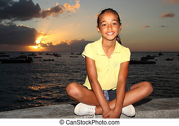 Girl sitting by the sea at sunset