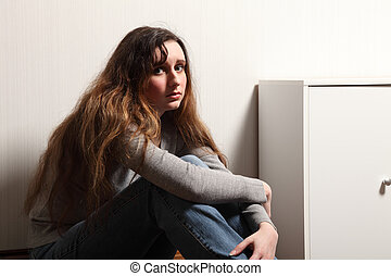 Teenage girl depressed sitting on floor at home - Teenage...