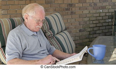 Elderly Man Reading Bible - Elderly man sits on his patio...
