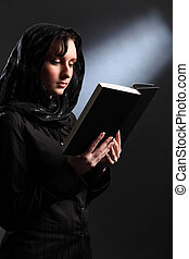 Religious young woman in headscarf reading bible - Beautiful...