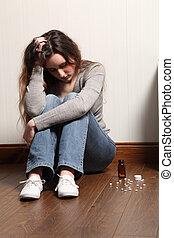 Teenage girl depressed sitting with pills on floor - Teenage...