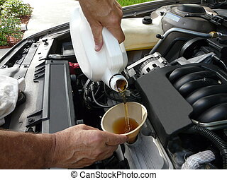 Adding Oil to a Car - Male adding oil with a funnel after a...