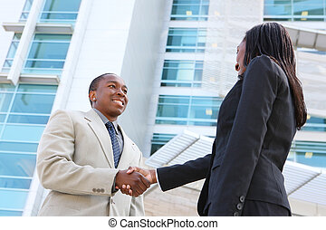 African Business Team Handshake - An african american...