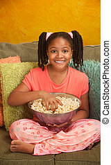 Little Kid Eats Popcorn - Little African American girl eats...