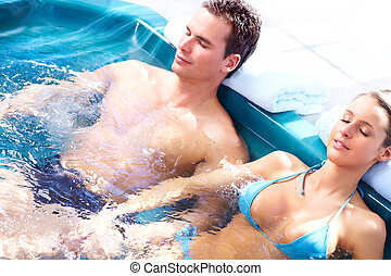 Couple in jacuzzi - Young loving couple relaxing in a...