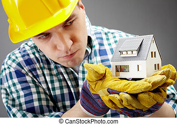 Constructor with house model - Portrait of a serious...