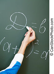 Writing formula - Hand of student writing formula on...