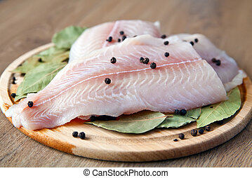 Pangasius - close-up raw fish pangasius with black pepper...