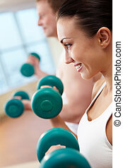 Weightlifting - Image of smiling woman and guy doing lifting...