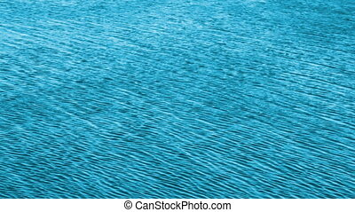 turquoise water background with sun reflections