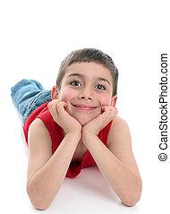 Cute smiling boy relaxing looking ahead