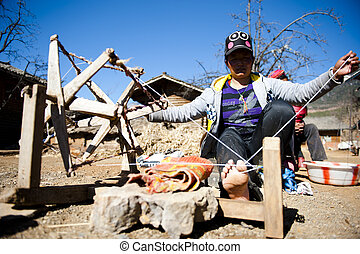 woman Spinning wheel in sunshine - asian woman Spinning...