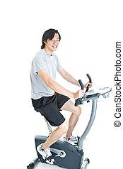Asian Man Riding Stationary Exercise Bike Isolated